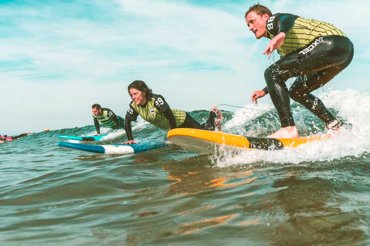 Young people surfing waves with Latas Surf School in Somo Spain