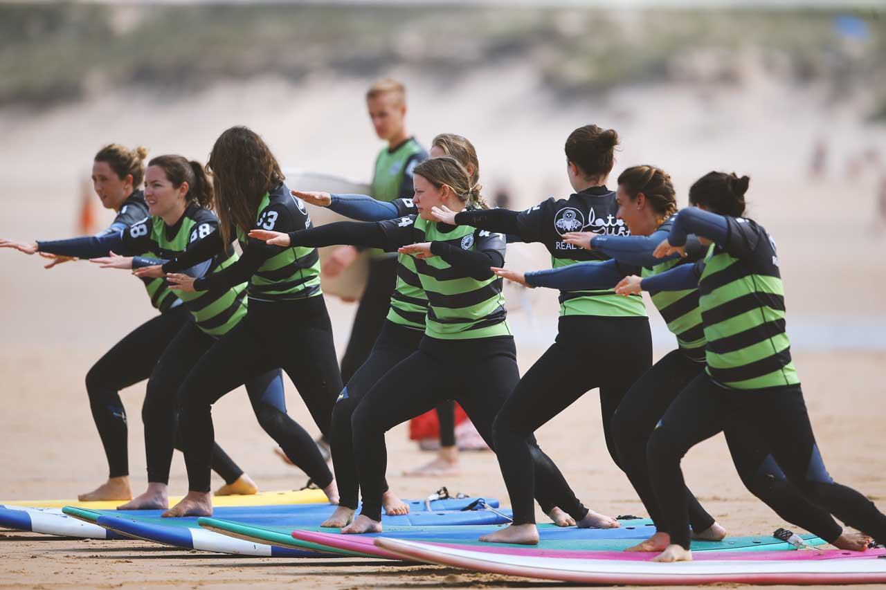 Group of surfer girls on a surf trip taking lessons at Latas Surf School in Somo Spain