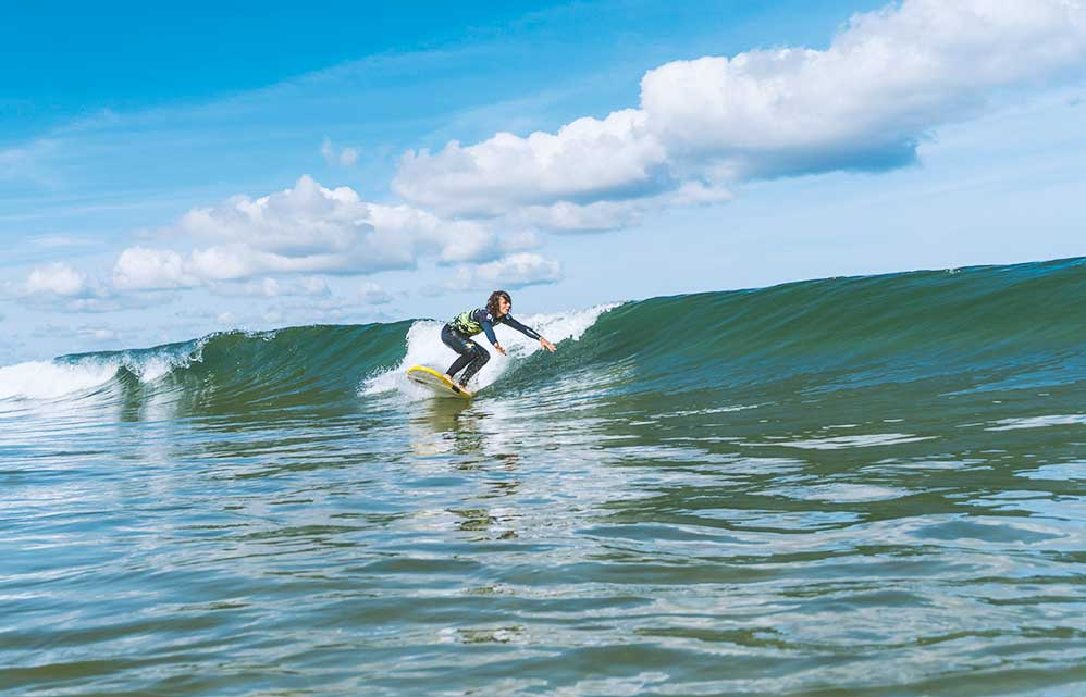 Surfer girl riding a wave at Loredo and Somo beach in Spain with Latas Surf School