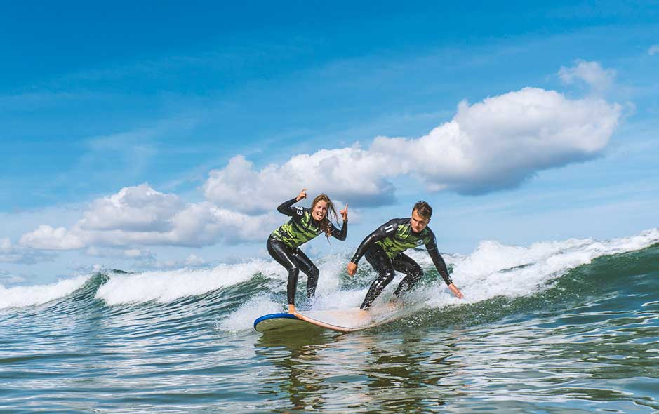 Couple surfing waves at Somo and Loredo beach with Latas Surf School in Spain