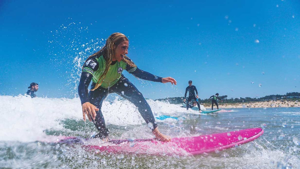Girl takes surfing lessons for beginners at Latas Surf School in Somo and Loredo, Spain