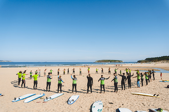 A group of peple warms up before a surfing lesson